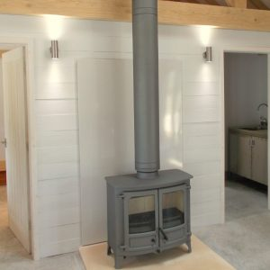 Charnwood Island 3 multi fuel stove in gun metal finish on bath stone hearth with vlaze panel