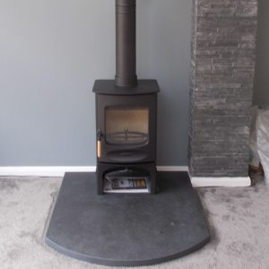 Charnwood C Four on log store standing on riven slate hearth