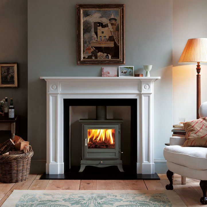 Wood Burning Stove in fireplace surrounds in a living room