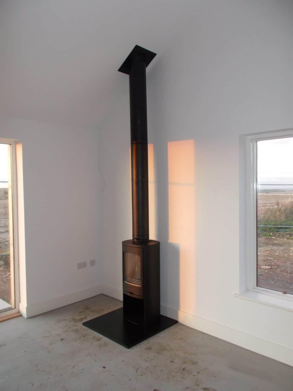 Black Contura 810 woodburner, black twin wall flue installed in barn conversion