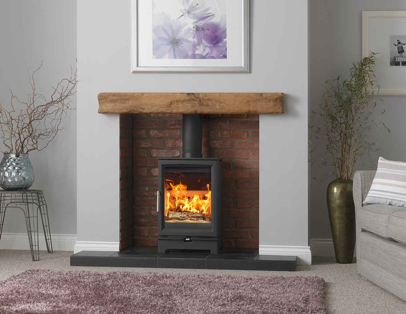 Fireline Woodtec 5kw wood burning stove in a chamber with a wooden beam above